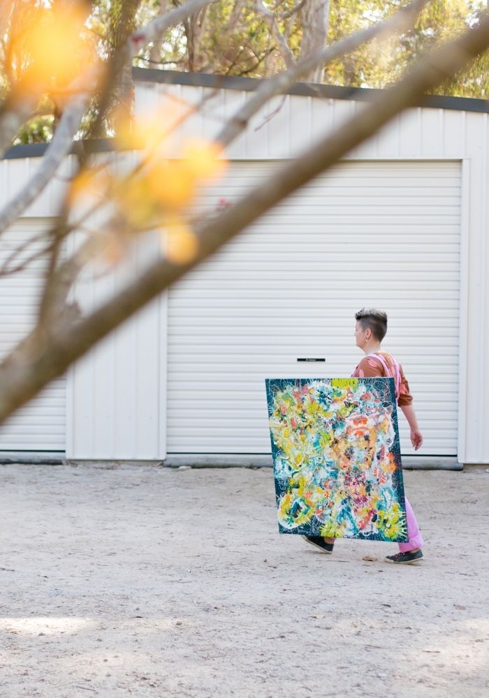 Tina_Denti_walking_in_front_of_garage_holding_canvas